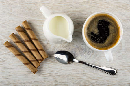 Few striped wafer rolls with chocolate filling, jug of milk, black coffee in cup, teaspoon on wooden table. Top view