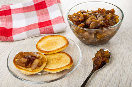 Checkered napkin, small pancakes with jam in transparent saucer, bowl of apple jam with cinnamon, teaspoon on wooden table