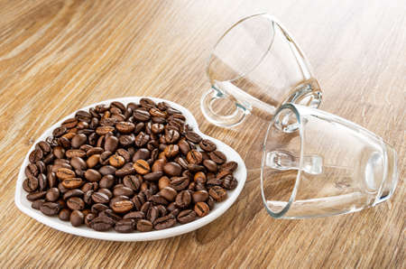 Roasted coffee beans in white saucer in heart shape, two empty transparent cups on brown wooden table