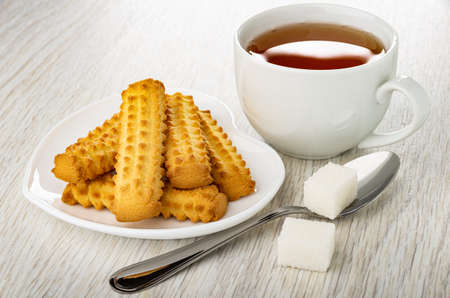 White plate in heart shape with shortbread cookies, teaspoon, sugar cubes, white cup of tea on wooden table