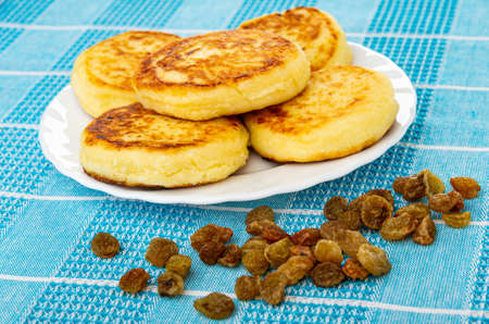 Few cottage cheese pancakes in white plate, scattered raisin on blue checkered napkin Archivio Fotografico