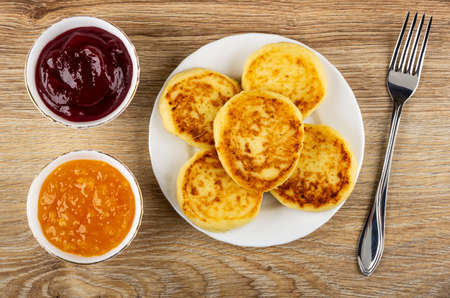 White bowls with cherry jam, orange jam, white plate with cottage cheese pancakes, fork on brown wooden table. Top view