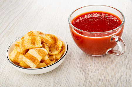 Potato chips, imitation of bacon in white bowl, transparent cup with tomato juice on wooden table