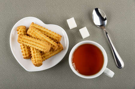 White plate in heart shape with shortbread cookies, sugar cubes, teaspoon, white cup of tea on gray table. Top view