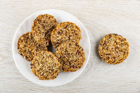 Round cookies with different seeds in white plate, cookie on wooden table. Top view