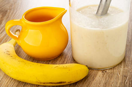 Banana, yellow pitcher with milk, electric blender in transparent glass with blend from banana and milk on wooden table Archivio Fotografico