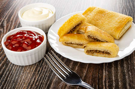 Bowls with mayonnaise and ketchup, whole pancake roll, pieces of fried pancake with meat filling in white plate, fork on dark wooden table Archivio Fotografico