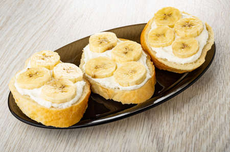 Three sandwiches with cottage cheese and banana in brown oval dish on wooden table