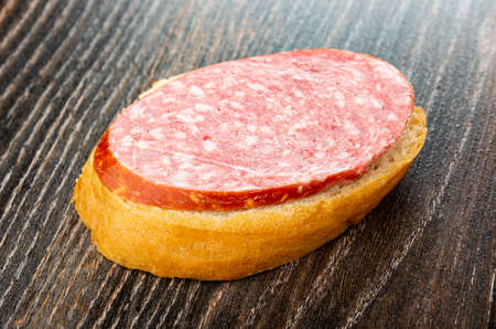 Sandwich with boiled-smoked sausage on dark wooden table