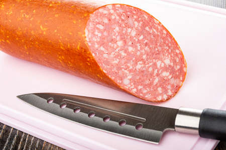 Piece of boiled-smoked sausage, kitchen knife on plastic pink cutting board Archivio Fotografico