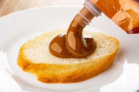 Pouring slice of bread boiled sweet condensed milk from plastic pack  in white plate