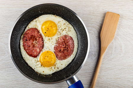 Fried eggs with sausage in frying pan, spatula on wooden table. Top view Archivio Fotografico