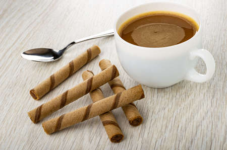 Teaspoon, coffee with milk in white cup, few brown striped wafer rolls with chocolate filling on wooden table