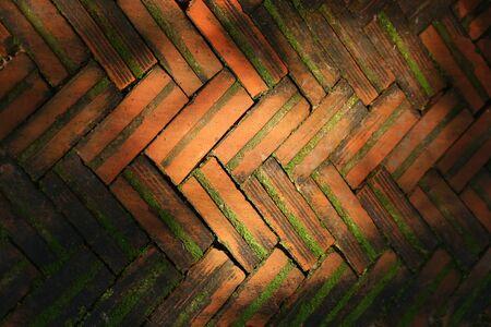 Orange bricks arranged alternately With moss growing and sunlight falling