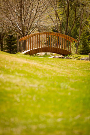 Bridge over small stream with grass field in front  photo