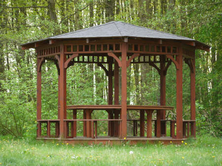 entrance arbor: Small brown wooden arbour at edge of forrest