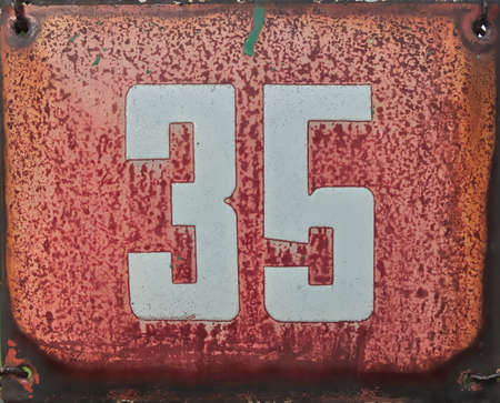 35: Old red rusty metal label with number 35