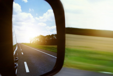 moving truck: Rearview Mirror View on the Hightway and Blue Sky , Clouds and morning Sun Stock Photo