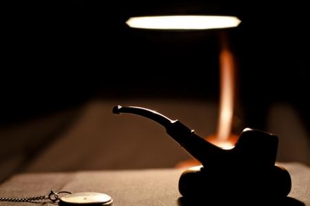 Smoking pipe silhouette in darkness in Desktop Lamp Light