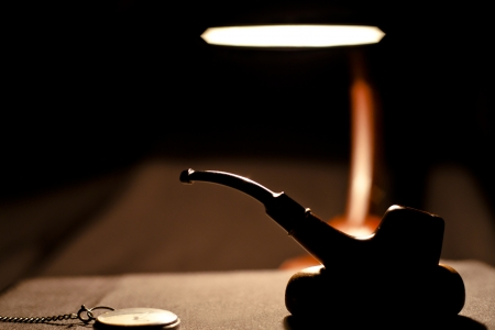 Smoking pipe silhouette in darkness in Desktop Lamp Light