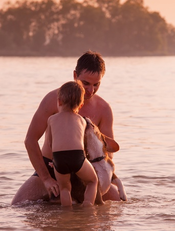 Father and son full around with beagle dog in the river water