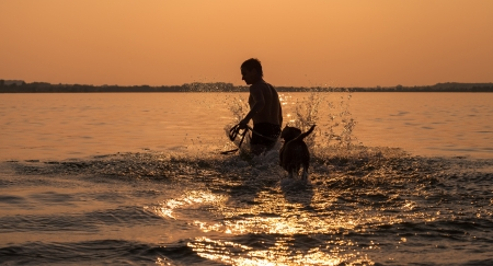 Man with little beagle puppy fooling around in ocean sunset waves photo