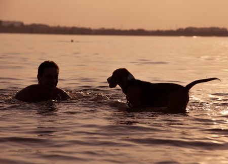 Evening sunset  boy with puppy in waves 스톡 콘텐츠