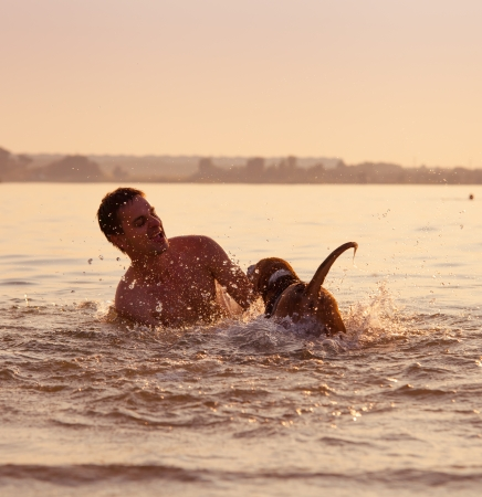 man with little beagle puppy fooling around in ocean sunset waves