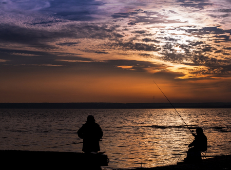 Fisherman on the calm Sunset seaside