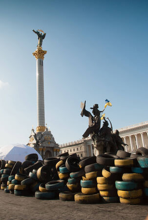 KIEV, UKRAINE - May 12, 2014: Ukrainian revolution. Euromaidan. Baricades maiden from old tyres painted national flag colors with The Monument of Independence of Ukraine on the background on the Maidan Nezalezhnosti on 12 MAY 2014 in KIEV,UKRAINE