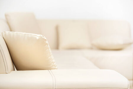 Beige leather sofa with pillows in the living room
