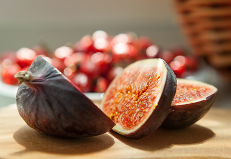Chopped Fig fruits on the cutting board with briar (dog rose) on the plate