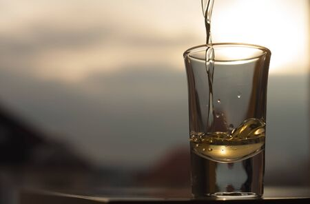 A golden alcoholic beverage being poured into the glass