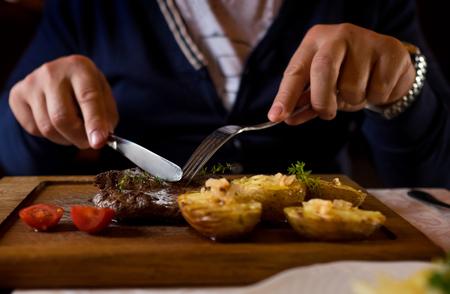 Man started eat medium roasted veal steak . Hands close-up view.  스톡 콘텐츠
