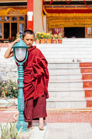 Thiksey village in Ladakh, India - AUGUST 20: The portrait of young monk standing near the New Hall of Thikse Monastery on August 20, 2016 in Thiksey village in Ladakh, India