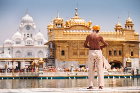 Sikh pilgrim prepearing to immerse in holy tank near Golden Temple (Sri Harmandir Sahib), Amritsar