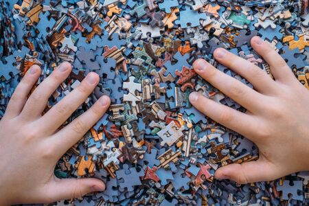 Childrens hands on Jigsaw puzzle color background