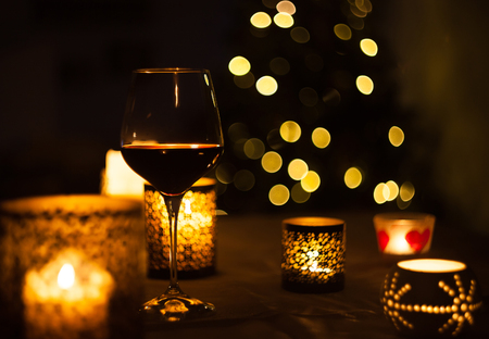 Red wine glass with christmas tree background