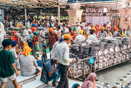 Amritsar, India - August 15, 2016: Pilgrims People come in and out Free canteen in Amritsar. This is the biggest free eatery in the world in Golden Temple, Amritsar, India