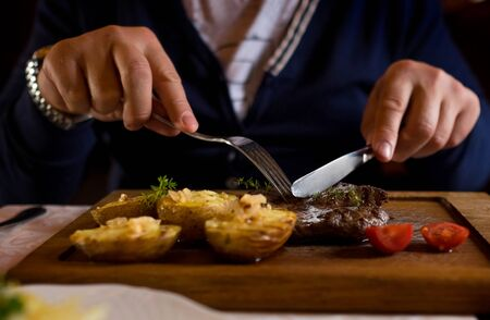 Man started eat medium roasted veal steak . Hands close-up view.  Stock Photo