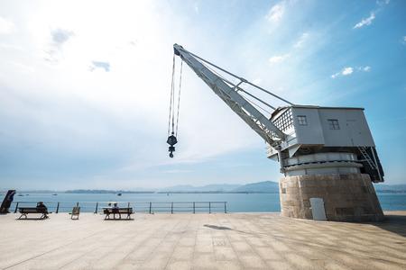 Santander (Spain) sea industrial embankment crane wide angle view.