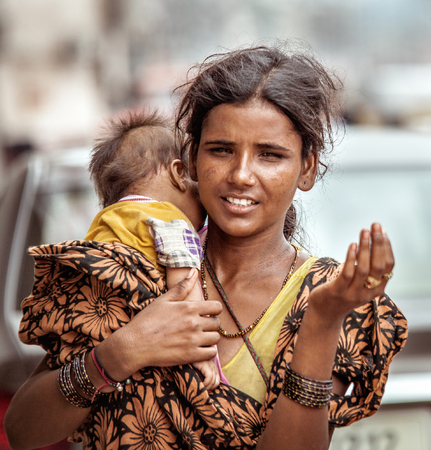 New Delhi, India - August 14, 2016: Young indian beggar woman with baby begs the alms in New Delhi, India