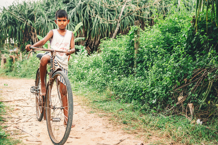 Weligama, Sri Lanka - December 21 , 2017: Little barefoot boy stands near the old rusty bicycle and poses for a photo in Weligama, Sri Lanka Editorial