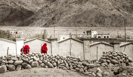 Group tibetan monks in red robes goes by the colorless lanscape Imagens