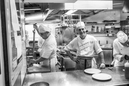 Venice, Italy - March 28, 2016: Small Italian pizzeria kitchen staff preparing the meals. Chief cook looks into a camera and smiles in Venice, Italy Editorial