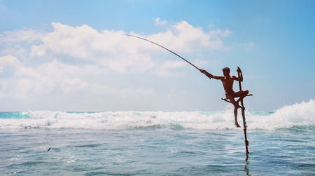 Sri lanka traditional stick- method fish catching Fisherman in the Indian Ocean waves.