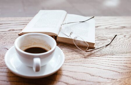 Still life image of cup of black coffee on saucer with vintage book and eyeglasses on the wooden table next to big coffee shop window. Banque d'images - 131759396