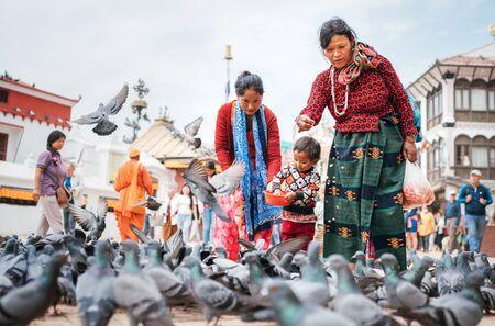 Kathmandu, Nepal - October 20, 2019: Portrait of colorful dressed nepali family feeding a pigeons on the square near Boudhanath, Kathmandu, Nepal.