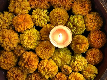 Tealight Candle Diya With Marigold Flower Floating in Water Inside Large Bowl. Happy Diwali - Hindu festival of lights.