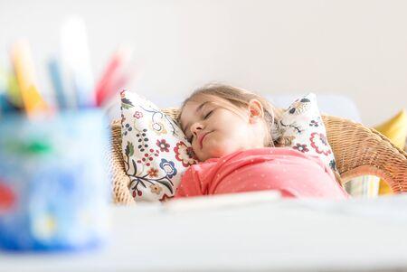 Tired little preschooler girl sleeping in comfortable chair near desk
